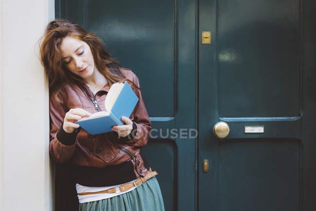 Frau liest ein Buch vor einer Tür — Stockfoto