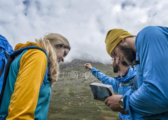 UK, Seenplatte, Great Langdale, drei Wanderer mit Tour guide auf Hecht von Stickle — Stockfoto