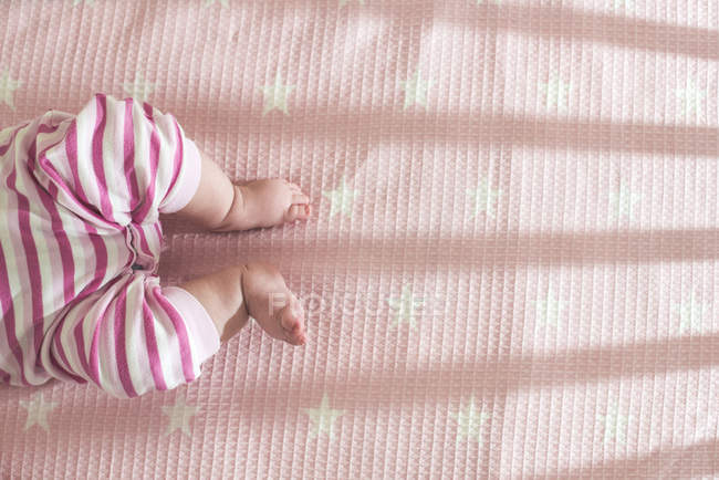 Cropped view of baby lying in pink cot — Stock Photo