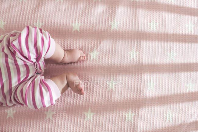 Vue recadrée du bébé couché dans un lit rose — Photo de stock