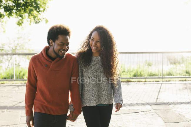 Портрет счастливой молодой пары, идущей рука об руку — стоковое фото