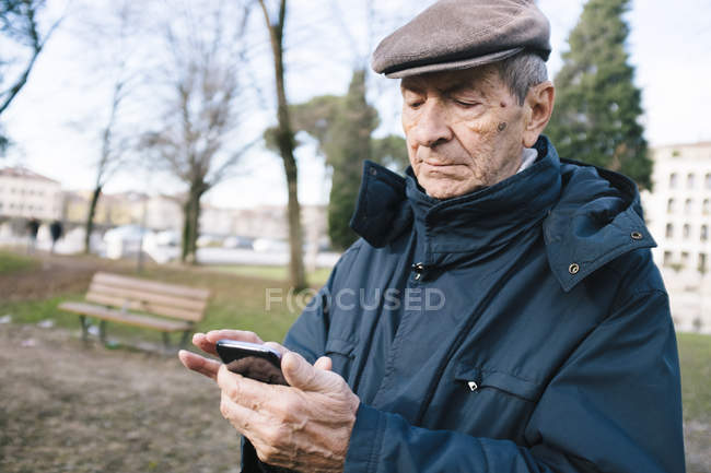 Portrait of senior man with smartphone in a park — Stock Photo