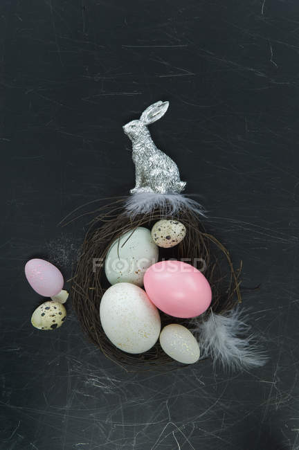 Easter nest with easter eggs, silver Easter bunny and feathers — Stock Photo