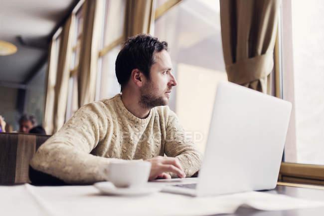 Hombre con portátil sentado en una cafetería mirando por la ventana - foto de stock
