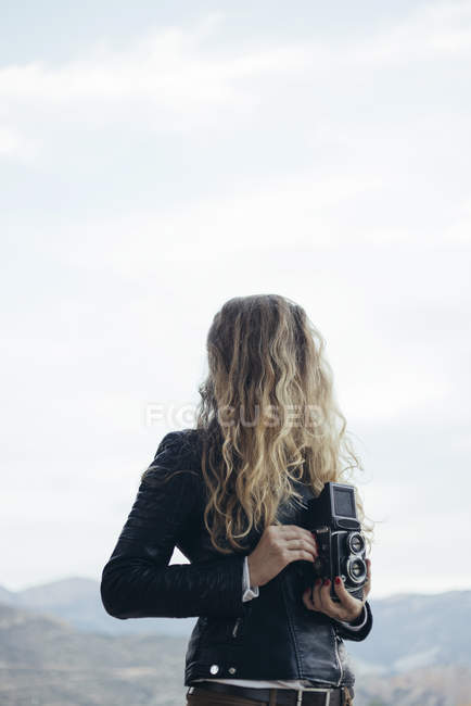Woman with obscured face holding vintage camera — Stock Photo