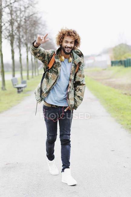 Portrait of happy man with dyed ringlets wearing camouflage jacket — Stock Photo