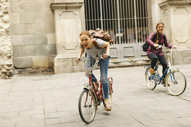 Two happy young women riding bicycle in the city — Stock Photo