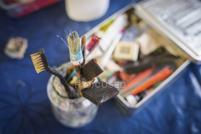 Mug with paintbrush and tools — Stock Photo