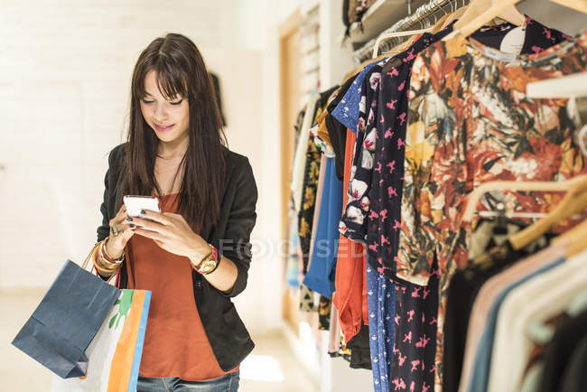 Young woman in fashion boutique using smart phone — Stock Photo