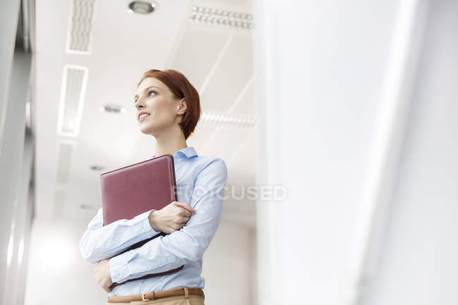 Businesswoman looking out of office window — Stock Photo