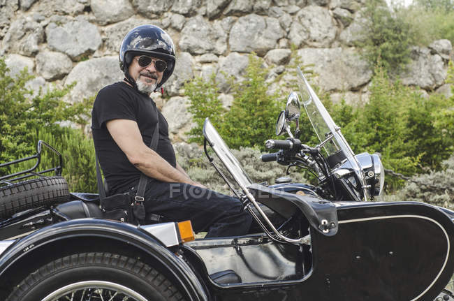 Confident mature man on sidecar motorbike — Stock Photo