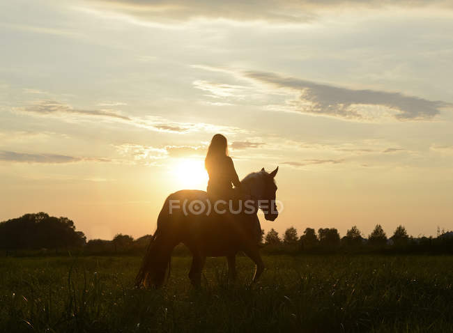 Young woman riding into the sunset — Stock Photo
