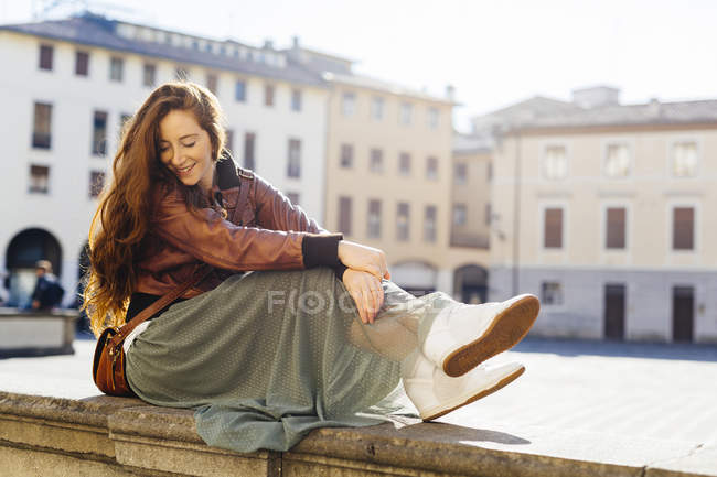 Italy, Padua, woman sitting outdoors at town square — Stock Photo