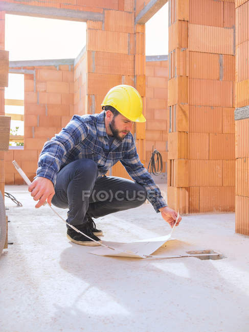 Foreman with construction plan and pocket rule at construction site — Stock Photo