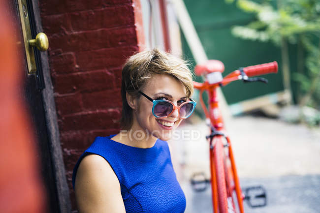 Portrait of smiling blond woman with sunglasses on her nose tip — Stock Photo