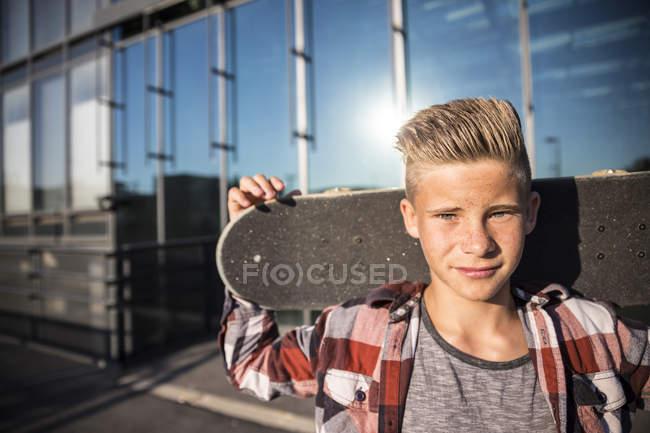 Portrait of caucasian teenager boy holding skateboard — Stock Photo