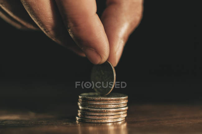 Hand holding coin on top of stack of coins — Stock Photo