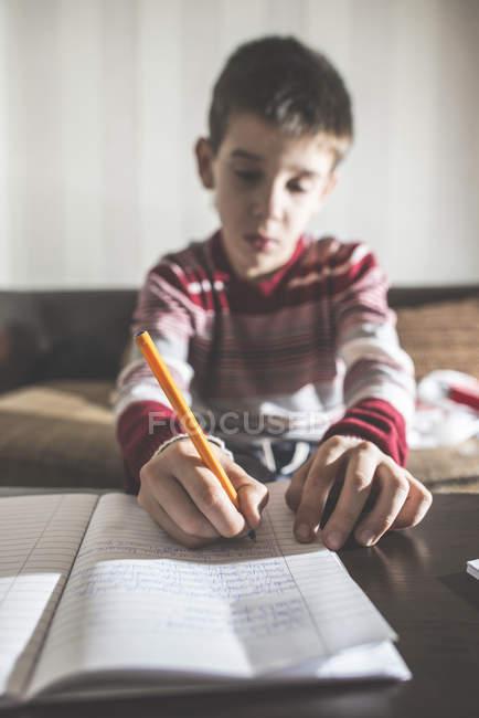 Портрет сумно хлопчик писати в Блокноті — стокове фото