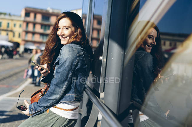 Woman at the bus stop holding a cell phone — Stock Photo