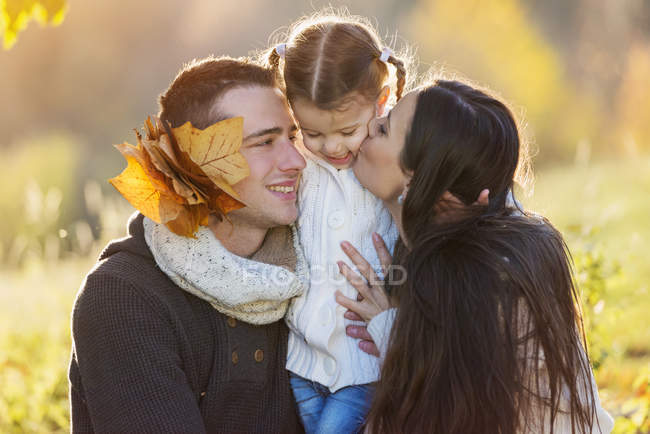 Happy family hugging in autumnal park — Stock Photo