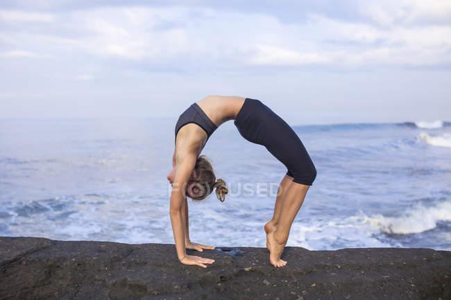 Indonesia, Bali, woman practising yoga at the coast — Stock Photo