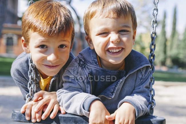 Deux garçons heureux sur une balançoire à l'aire de jeux — Photo de stock