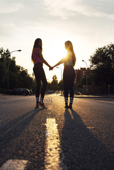 Two female friends standing hand in hand at sunset — Stock Photo