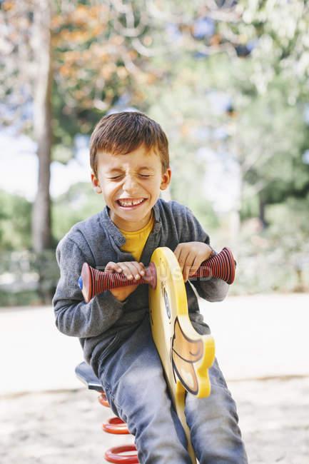 Веселый мальчик, развлекающийся на детской площадке — стоковое фото