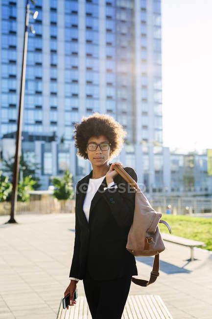 Portrait de femme d'affaires avec sac debout dans la rue — Photo de stock