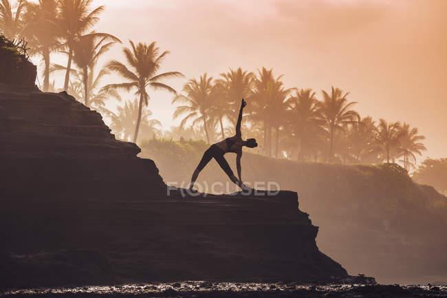 Indonesien, Bali, Frau praktiziert Yoga an der Küste in der Dämmerung — Stockfoto