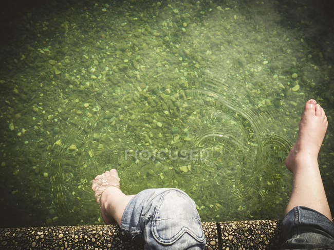 Girl's feet at the edge of a lake — Stock Photo