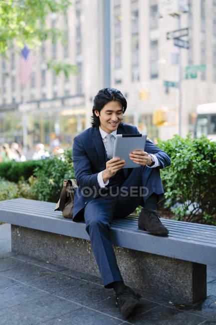 Uomo d'affari sorridente guardando tablet digitale — Foto stock