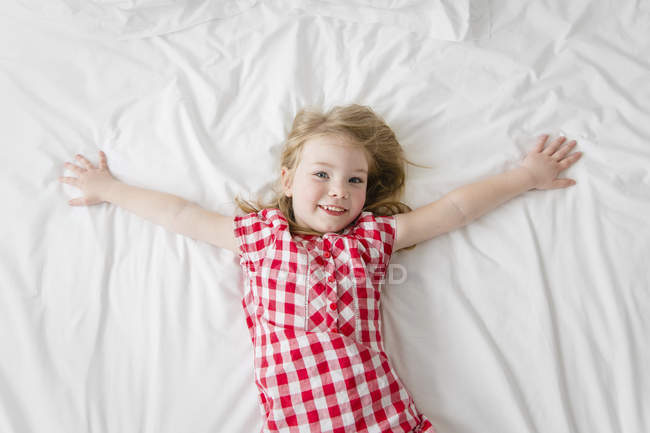 Porträt von lächelnden kleinen Mädchen auf einem Bett liegend, mit ausgestreckten Armen — Stockfoto