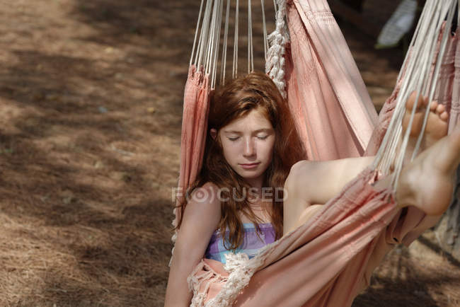 Portrait of girl with closed eyes lying in a hammock — Stock Photo