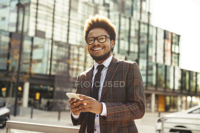 Smiling young businessman outdoors with cell phone — Stock Photo
