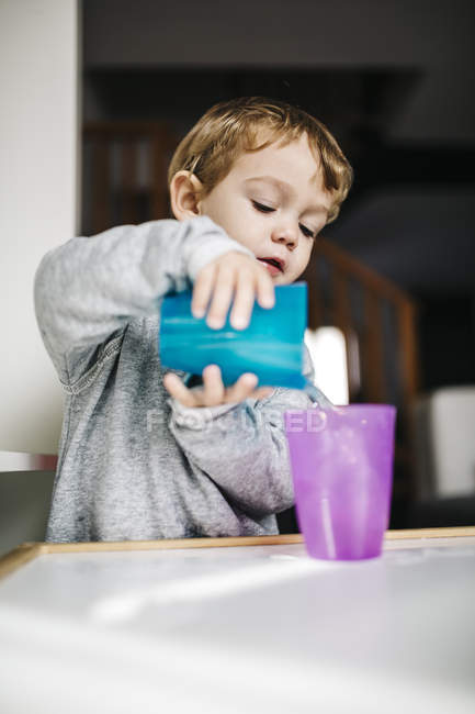 Boy playing with cups and water — Stock Photo