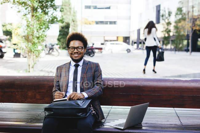 Jeune homme d'affaires souriant avec ordinateur portable et ordinateur portable sur banc — Photo de stock