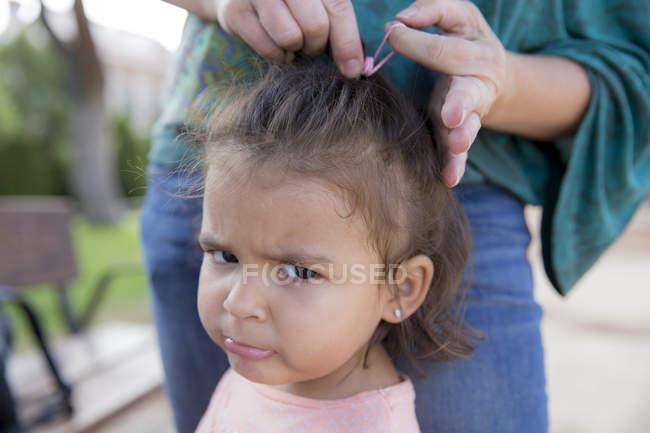 Primo piano di Madre legando capelli di piccola figlia — Foto stock