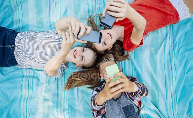 Trois amis adolescents avec des smartphones couchés sur une couverture — Photo de stock