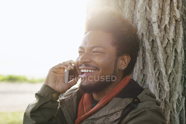Portrait of smiling young man leaning against tree trunk telephoning with smartphone — Stock Photo
