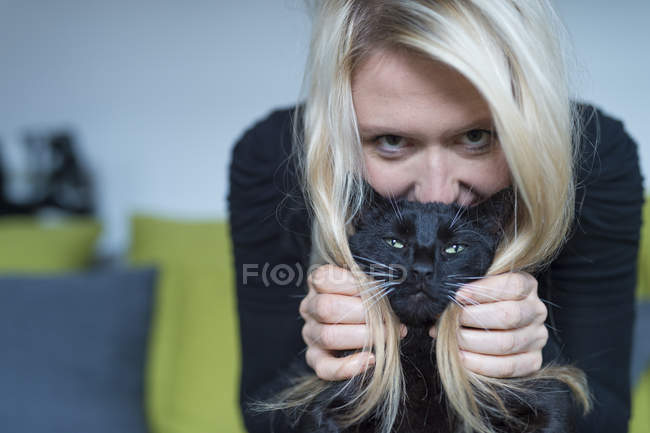 Portrait of blond woman and her black cat — Stock Photo