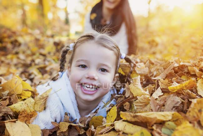 Chica feliz en hojas de otoño - foto de stock