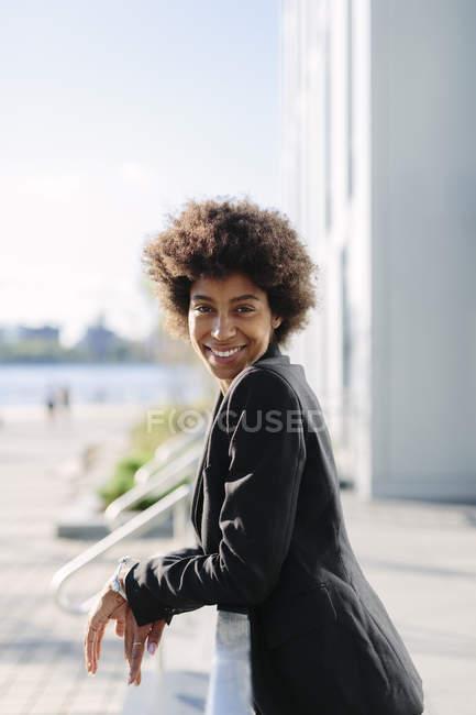 Porträt einer lächelnden Geschäftsfrau, die sich an Geländer lehnt — Stockfoto