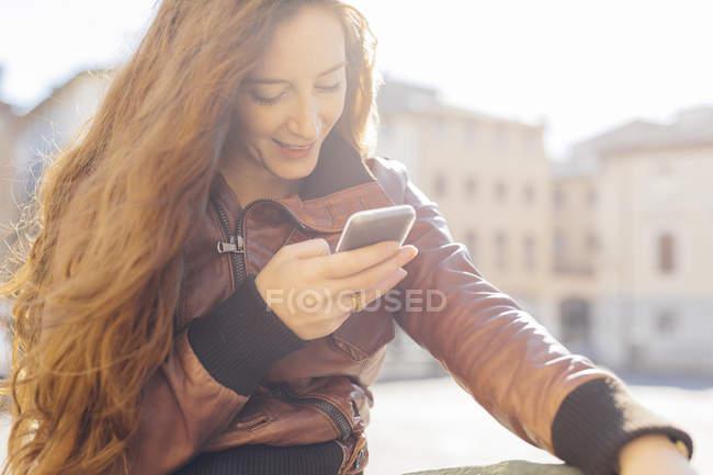 Mulher olhando ao ar livre para celular — Fotografia de Stock