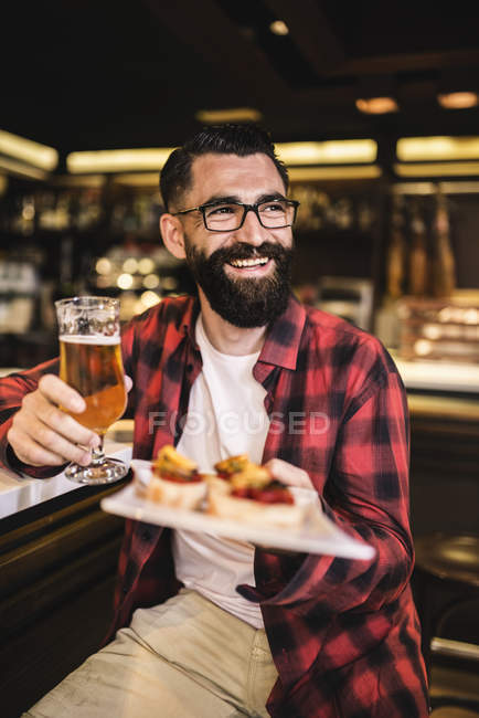 Portrait of happy hipster with glass of beer and tapas sitting at counter in a pub — Stock Photo