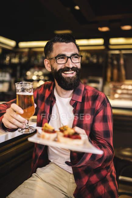Ritratto di felice hipster con bicchiere di birra e tapas seduto al banco in un pub — Foto stock