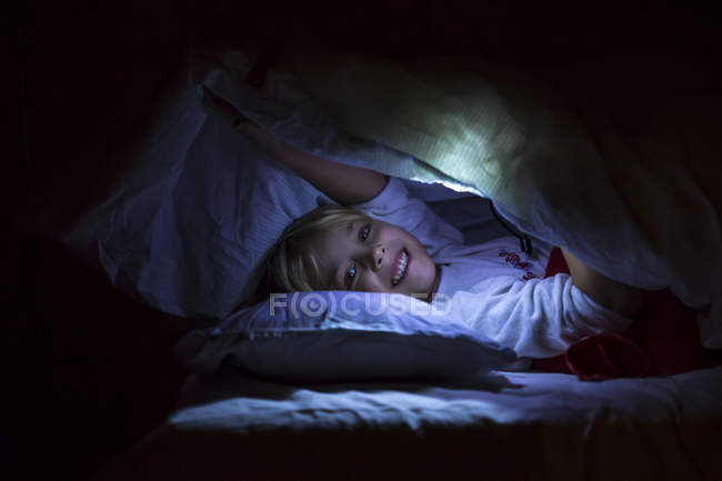 Girl with lighting torch in bed — Stock Photo