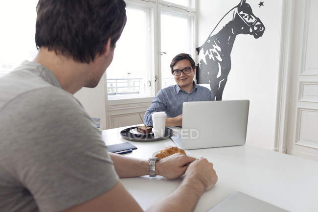 Two creative businessmen having a meeting in a modern office — Stock Photo