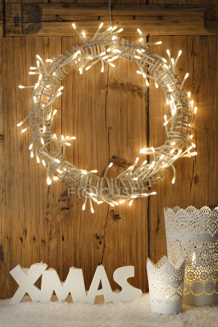 White Christmas decoration with lighted Advent wreath in front of wooden wall — Stock Photo