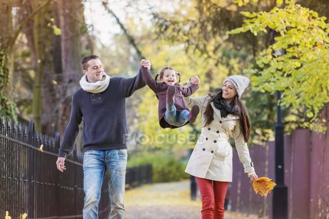Padres levantando hija en el parque otoñal - foto de stock